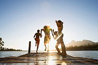 Family, in swimwear, running along jetty, jumping into lake at sunset, rear view surface level, lens flare