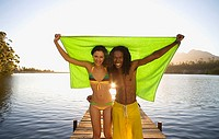 Couple standing on lake jetty, arms around each other, holding aloft green towel, smiling, front view, portrait