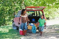 Father and son 8-10 unloading parked SUV on camping trip, sharing load of picnic hamper, smiling