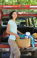 Woman unloading parked SUV on family camping trip, carrying picnic hamper, smiling, portrait