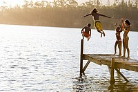Father and son 8-10, in swimwear, jumping off jetty into lake at sunset, mother and daughter 7-9 cheering, rear view