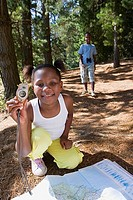Girl 7-9 kneeling on woodland trail, looking at map, using compass, smiling, portrait, brother 8-10 in background