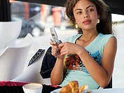 Teenage girl 14-16 sitting in cafȽ, holding mobile phone, daydreaming