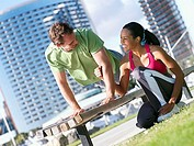 Couple exercising in park, man doing press-ups on bench, woman offering encouragement, smiling tilt