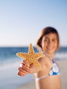 Girl 10-12 holding aloft starfish on sandy beach, smiling, portrait, focus on foreground