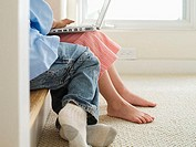 Boy 5-7 and mother using laptop at bottom of stairs in hallway, side view, low-section