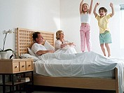 Parents lying in double bed at home, two energetic children 5-8 jumping up and down on bed, smiling