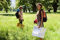 Young couple, with rucksacks, standing in woodland clearing, departing on hiking trip, woman holding map, smiling, portrait