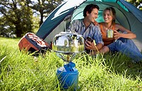 Young couple sitting inside dome tent in woodland clearing, waiting for kettle to boil on camping stove, smiling