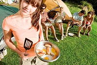 Five young adults eating fried breakfast beside tents on camping trip, focus on woman with pan and spatula, portrait tilt