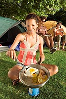 Young adults eating fried breakfast beside tents, focus on woman with spatula cooking on camping stove, portrait tilt