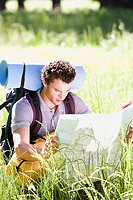 Young man, with rucksack, sitting in woodland clearing, consulting map on hiking trip