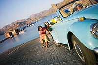 Two teenage girls 17-19 pushing blue car, lake in background, teenage boy steering tilt