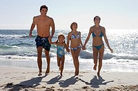 Two generation family wearing swimwear, walking away from surf on sandy beach, side by side, holding hands, front view, smiling