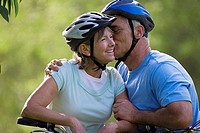 Active senior couple in cycling helmets sitting on bicycles, man kissing woman on cheek, smiling