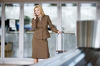 Businesswoman with luggage using mobile phone in airport baggage claim area, smiling