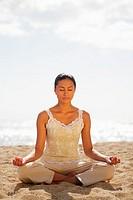 Girl on beach meditating