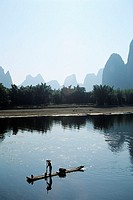 China, Li River, near Yangshou, Local man floating on bamboo raft