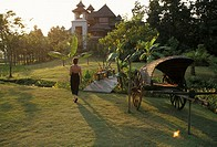 Thailand, Chiang Mai, The Regent Resort, Woman walking on front lawn, Warm afternoon lighting