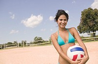 Woman holding volley ball on beach (thumbnail)