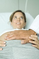 Pregnant woman lying on back, doctor´s hand on stomach