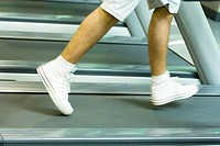 Man running on treadmill, knee down, blurred motion
