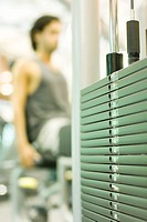 Man working out with weight machine, focus on weights in foreground