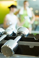 Dumbbells on rack, women in blurred background