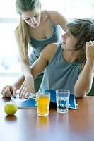 Young adults in exercise clothing having snack in health club cafeteria, looking at magazine