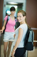 Young woman with backpack, smiling at camera