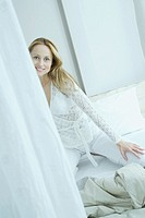 Woman kneeling on unmade bed, smiling at camera