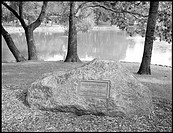 Large rock as headstone near a pond in a cemetary