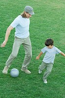 Man and boy playing soccer on grass