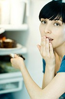Young woman taking slice of cake from refrigerator, looking at camera, covering mouth
