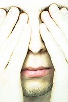 Young man covering eyes, extreme close-up