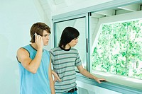 Teenage friends standing by window, one using laptop (thumbnail)