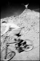 Blurred bike rider on rough terrain with figure in distance