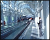 Out-of-focus view of businessman on cell phone in airport