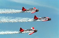 Three stunt planes fly in close proximity to one another, emitting thick plumes of smoke´