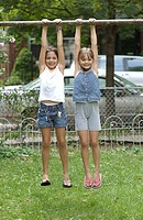 Two girls hanging from outdoor horizontal pole
