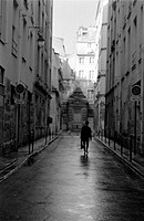 Silhouette of man with briefcase walking down Paris street