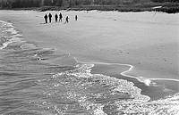 Family walking along beach in fall