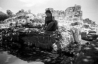 Woman sitting on ruins near Cancun, Mexico´
