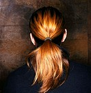 Man with strawberry blonde hair in ponytail faces wall