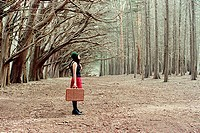 Woman standing in forest with suitcase