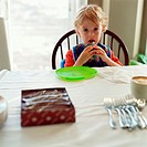 Young boy eating cupcake at dinner table