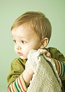 Portrait of baby boy holding blanket, close-up