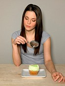 Young woman looking at cake with magnifying glass