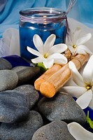 Spa elements, candle, flowers, Hawaiian hula sticks and grey stones