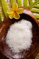 Spa elements, koa bowl filled with raw salt, garnished with yellow plumeria and leaf on lauhala mat